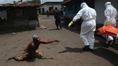 Monrovia, Liberia, 10 de octubre de 2014. Una mujer postrada en el suelo, extiende un puñado de tierra hacia el cuerpo de su hermana que va a ser incinerada tras fallecer a causa del Ébola.