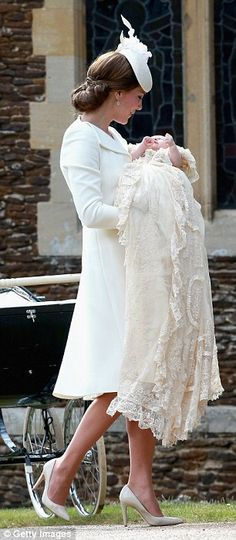 Beautiful: The Duchess of Cambridge carries her baby daughter into the church in the gown...