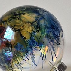 Alcohol inks blown with canned air on clear Christmas ornament.