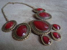Colar confeccionado em metal na cor ouro velho com aplicação de chatons de acrílico vermelho.  Altura regulável  Comrpimento: 46cm + 6,5cm de corrente alongadora R$82,90