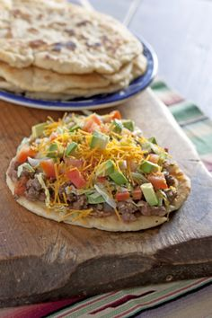 Fry Bread Tacos - These fry bread tacos are similar to Tacos de Picadillo, but instead of fried corn tortillas, these tacos are made with fry bread. Fry bread is a Native American staple. After the dough is fried the flat taco shells are smothered with homemade refried beans and topped with picadillo, lettuce, cheese, and tomatoes.