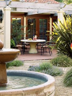 Just outside this home's kitchen is a patio for casual meals. Paved with saltillo tile, it overlooks the courtyard, with its cooling custom-designed fountain. (Photo: Thomas J. Story)