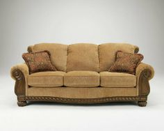 "Burnham - Amber Collection Stationary Sofa by Famous Brand Furniture. $737.34. Warm earth tone upholstery. Plush rolled arms. Carved legs and apron. 91.00"" W x 41.00"" D x 40.00"" H. Traditional bun feet. You will love the traditional style of this stationary sofa from the Burnham-Amber collection. Features plush rolled arms, thick supportive cushions and coordinating throw pillows. Ornately carved apron and legs and bun feet complete the look. Sofa only. Matching pieces sold ..."