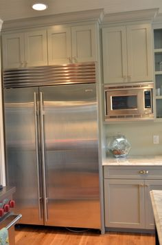Cabinets surrounding refrigerator come out slightly further than other cabinets to fit the refrigerator better.