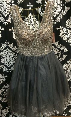 Beautiful tulle baby doll featuring a sheer mesh overlay accented with crystals and sequins along the bodice and jewel style neckline. Tulle skirt is finished with a fish line hem. Back zipper closure.  Exclusive dress to Crown to Heels. Available in Gunmetal/Nude.