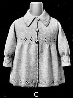 A girl's coat with eyelet design on the cuffs and around the hem and waist, the cuffs and hem done in a contrast colour. The coat is knitted in pieces from the bottom up, while the sleeves are knitted from the top down and sewn in. The collar is knitted separately in the contrast colour and sewn on.