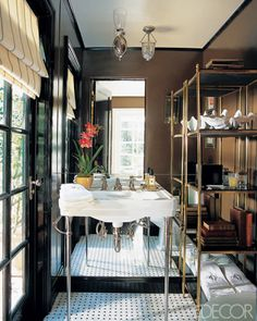 Chocolate brown walls (Fine Paints of Europe's Dutch Chocolate), black trim and doors, mirrored wall, brass etagere, Waterworks washstand, petite bell jar lantern, tiled floors - Mike Clifford's powder room - Elle Decor, October 2012