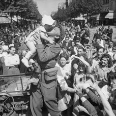 An AFPU photographer kisses a small child before cheering crowds in Paris, 26 August 1944.