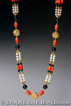 CARTIER  A magnificent gold, onyx, coral and pearl sautoir necklace,  composed of five open work textured 18 karat gold beads, interspersed with cultured pearls, onyx and carved coral beads.
