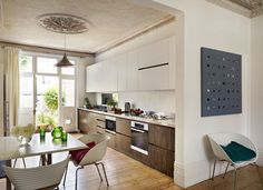 This contemporary two tone kitchen maximises storage without closing in the space. The cupboards have no handles to distract your eye and the top ones disappear into the background. Fantastic for a narrow contemporary space. Thoughts by Annika Nott