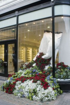 3D window display. A very visual visual design. The large garden glove is original, then the flowers flowing from the inside to the outside.
