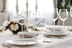 Elegant and simplistic table setting featuring white and yellow flowers and a silver candelabra.