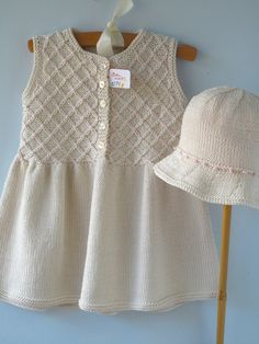 Classic Hand Knit Sleeveless Smock Dress with exquisite floral detailing The dress and hat combination featured in the photographs are a