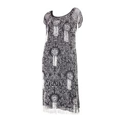 Vintage dress dates to the 1920's during the Art Deco era. It is made of black silk chiffon with pearly white bugle beads sewn throughout in a scrolling pattern. Beaded fringe throughout dress and at