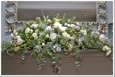 For the table arrangements, storm lanterns with church candles were placed in a Christmas ring of blue spruce, eryngium, eucalyptus, roses, hellebore's and dipped and waxed fruits. Description from weddingflowers-cotswolds.co.uk. I searched for this on bing.com/images