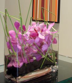 This is a cube vase floral arrangement that features pink mokara orchids with blades of grass atop black river rocks.  See our entire selection at www.starflor.com.  To purchase any of our floral selections, as gifts or décor, please call us at 800.520.8999 or visit our e-commerce portal at www.Starbrightnyc.com. This composition of flowers is generally available for same day delivery in New York City (NYC). SQ142