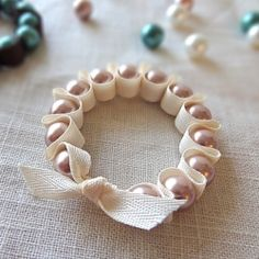Follow this simple tutorial to create three different versions of ribbon and pearl stretch bracelets.