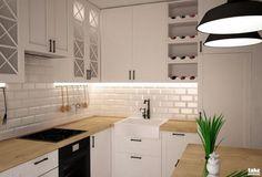 Aranżacja kuchni z białymi szafkami z miejscem na wino i klimatycznym…