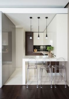 With the limited space, you wouldn't want to cut the line of vision and make your kitchen space look smaller. This small kitchen looks bigger than its actual size, thanks to the transparent bar stools and predominantly white colour scheme