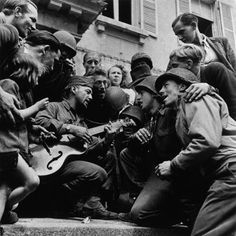 American soldiers and French citizens celebrating the town's liberation in front of City Hall; Cherbourg, France - 28 June 1944    Photo by Robert Capa