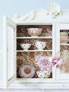 Wallpaper your cabinets. Cover the back of your glass-front or open cabinets with wallpaper remnants or pretty contact paper to give collectibles and fine china an elegant backdrop. Tip: In kitchens, vinyl wallpaper makes for easier cleanup.