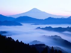 Distant view of Mount Fuji silhouetted against blue sky - Fotografiskt tryck på AllPosters.se