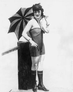 Bathing suits through the years: 1918 ( Photo by American Stock/Getty Images ) A 'bathing beauty' from film director/producer Mack Sennett's stable wearing halter-style striped swimsuit, knee socks and laceup shoes, poses with a parasol on a boardwalk Vintage Bathing Suits, Vintage Swim, Vintage Black, Vintage Glamour, Vintage Ladies, American Stock, Bathing Costumes, Striped Swimsuit, Vintage Photographs