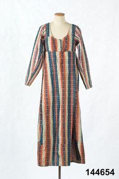Folklig variant på empirklänning 1803 Hel klänning i empirmodell. Av hemvävt halvylletyg i tuskaft med breda ränder i munkabälte. Varp av blåvitt lingarn med inslag av entrådigt ullgarn i vitt med ränder i brunrött, rött och blått. Ärmarnas och ryggens tyg skiljer sig något i färg där ränderna endast är i blått och rosa.