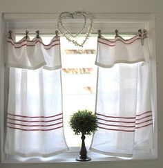Vintage tea towels as curtains  run clothes line wire and clip with clothespins.