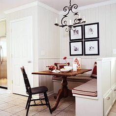 I like the chandlier.  An awkward space proved to be the perfect location for an L-shaped banquette. The recessed wall on the other side of a door added square footage, but the question was what to do with it. The space was transformed into a family-friendly kitchen dining space. The antique table and chair is charming and graceful. As a bonus, drawers beneath the bench add storage.
