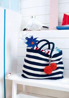 Un grand cabas tricoté avec rayures bleu marine et blanc et pompons rouges accrochés avec un mousqueton