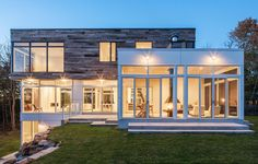 A Stunning Facade With Exotic Lighting Of Modern Three Storey House Design With Glass Window And Fascinating Furnitures A Large Three Storey House Exhibits Modern Luxury Home design