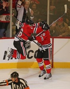 Patrick Kane #88 of the Chicago Blackhawks jumps into the arms of Patrick Sharp #10