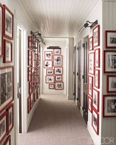 ELLE DECOR: How to Hang Art and Photos - Artwork and Photo Display Ideas | For a home in Southampton, New York, designer Steven Gambrel transformed a hallway into a gallery, with a display of disparate black-and-white family photographs unified by red frames. The custom framing is by Chelsea Frames in Manhattan, and the picture lights are by Alexa Hampton for Visual Comfort & Co.