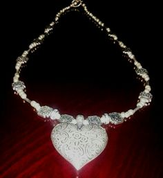 Heart pendant on silvery beaded necklace