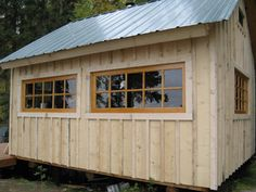 stained board and batten siding, metal roof, natural wood windows