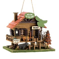 Let the call of the wild welcome birds into your yard with this adorable log cabin bird house. Fashioned after a vacation rental in the heart of the wilderness, it features rustic accents, including a