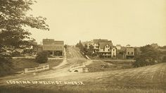 Looking Up Welch St - Postcard from about 1911. This view looks south across Boone Street (renamed Lincoln Way after 1914) towards Welch Street. Development in Campustown is just beginning. Lake LaVerne not yet constructed, the new bridge over College Creek connects the campus to Welch has just been constructed. To the left, the brick Champlin Building (1909) and Champlin Livery are visible. Friley Dorm now stands in the foreground to the right.  Courtesy of…
