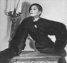 Lisa Fonssagrives in a slim navy-blue worsted poplin with double-file pockets and single file back-buttons, worn with a black fox stole all by Christian Dior, photo by Horst for Vogue, Feb. 1950