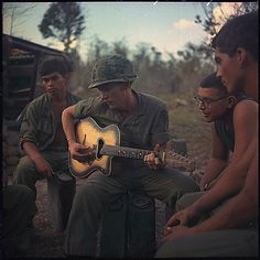 Following a long day, in 1968, a few soldiers gather around a guitar and play songs. Vietnam war.