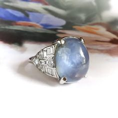 Found is this Art Deco blue-gray star sapphire ring with mixed cut diamonds in platinum. It is made up of a natural (some inclusions), 25.18ct. oval blue-gray star sapphire cabochon with faint star set in four prongs. There is a half-moon, bezel set diamond on each side (approx. total .28cts for