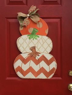 Tiered pumpkin door hanger with a different look for each of the 3 painted pumpkins. Would be cute personalized. Its perfect way to greet visitors to your home. Its made to order from mildew resistant hardwood plywood, primed, hand painted and sealed. It comes with a bow that is treated with scotch guard and has a wire hanger on top. Its ready to hang on the door and greet your guests. It measures 26x18.  Everything is hand painted and lettering is hand written. Please expect small…