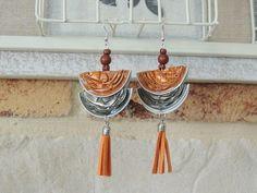 Boucles d'oreilles réalisé en capsules de café Nespresso de couleur orange et kaki, elle sont pliées en deux.  Elle est agrémentée de perles et d'un pompon orange.  Les s - 14623381