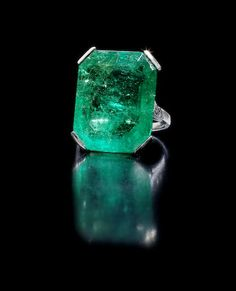 Stunning Art Deco emerald ring - The step-cut emerald, weighing 19.15 carats, is set with trios of brilliant-cut diamonds and mounted in platinum. French assay mark, ring size K. $32,226 incl. premium. Bonhams.