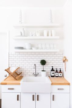 A clean and simple white kitchen with a tiled backsplash