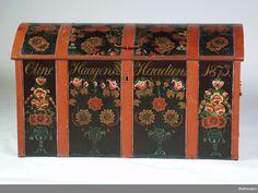 En brun kiste i furu med rødmalte jernbeslag. Mellom beslagene er det rosemaling i form av naturalistiske blomster. Kisten har buet lokk og c-formede håndtak . Den er tapetsert innvendig.