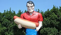 """Standing 19 feet tall and clutching a giant hot dog, this Paul Bunyon statue, not """"bunyan"""" purposely spelled with an """"o"""", is one of Route 66..."""