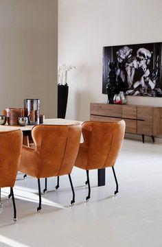 Rijke materialen en de kleurencombinatie neutrale tinten met fel oranje: deze leefhoek is voorzien van luxe meubels met een vleugje retro.