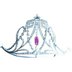 An unusual and high belle epoque tiara, 1900. Diamond greek key symbols teamed with scrolls and laurel leaves round a central rectangular ruby.