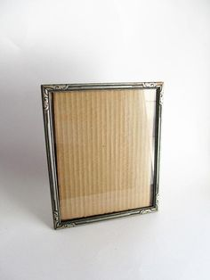 This frame is a beautiful example of an Art Deco design on gray toned wood. The frame is wood with dark gray accents in between the lighter gray that makes up the carved Art Deco design. Perfect for table top display. It holds an 8 x 10 picture. The glass is included. The back is covered in thick Shoe Shine Box, Victorian Dressers, Frame Gallery, Thick Cardboard, Vintage Picture Frames, Table Top Display, 10 Picture, Art Deco Design, Lighter